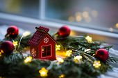 Red Wooden Toy House Surrounded With Fir-tree Wreath Decorated With Warm Garland Lights And Little C poster