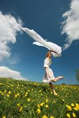 Girl jumps over dandelion field in nice summer day