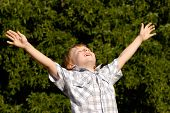 O menino com as mãos abertas levantada para o céu