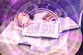 Close Up Of Hands Holding Glowing Book With Zodiac Wheel. Magic And Astrology Concept. Double Exposu poster