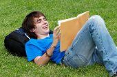 Guy Verlegung auf das Gras und ein Buch zu lesen
