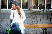Young smiling Woman sitting on Berm telefonieren mit Handy