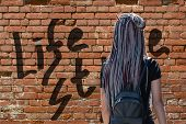 A Girl With Hair Braided In Braids Stands With Her Back And Looks At The Brick Wall. On A Brick Wall poster