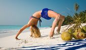 foto of bending over backwards  - A view of a young woman bending over backwards and stretching on a tropical beach with palm trees in the background - JPG