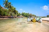 Beautiful view on small indian river with wooden outrigger fishing boats at Baga Beach, Goa, India