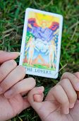 stock photo of soulmate  - A couple holding their fingers in front of the Lover tarot card - JPG