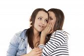 teenager whispering news to her sister