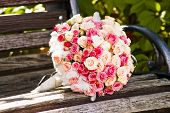 stock photo of trillium  - Wedding bouquet with roses on a wooden bench