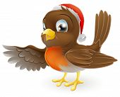 stock photo of robin bird  - Cartoon Christmas Robin bird mascot in a Christmas hat pointing with its wing - JPG