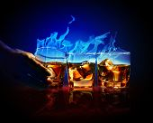 Image of three glasses of burning yellow absinthe