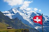 stock photo of snow clouds  - Swiss flag on the top of Mannlichen  - JPG