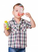 Boy Blowing Soap Bubbles On White