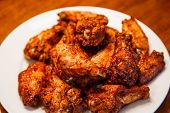 foto of mesquite  - A white plate of spicy mesquite flavored chicken wings - JPG