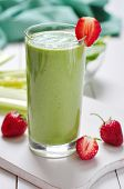 foto of celery  - Green vegetable smoothie with celery and strawberry on wooden background