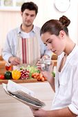 Young woman reading a newspaper while her boyfriend prepares lunch