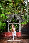 stock photo of ashtanga vinyasa yoga  - Yoga step of ardha baddha padmottanasana pose by fit man in white trousers near stone temple in tropical forest - JPG