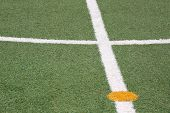 White Lines and a Yellow dot on green turf