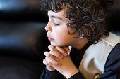 stock photo of praising  - Latino boy daily devotional - JPG