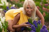 Beautiful blond  girl with violet spring flowers, amazing spring photo from Latvia, Baltic states, Europe