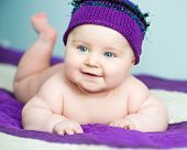 happy newborn baby girl in a purple  hat
