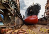 stock photo of shipyard  - A large tanker ship is being renovated in shipyard Gdansk Poland - JPG