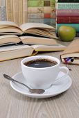 A Cup Of Coffee On A Table Among Books