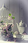 Vintage afternoon tea with birdcage filled with spring blossom