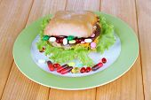 Conceptual image for nutritional care:assorted vitamins and nutritional supplements in bun. On woode