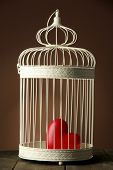 Heart in decorative cage on wooden table, on brown background