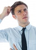 Thinking businessman scratching head on white background