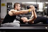 foto of muscle  - Personal trainer helping woman working with heavy dumbbells - JPG