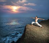 pic of virabhadrasana  - Yoga warrior pose by man in white trousers on the cliff near the ocean in Kerala India - JPG