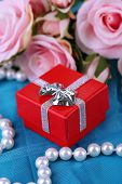 Rose and gift box on blue cloth