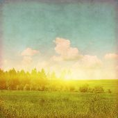 Summer landscape at sunset in grunge and retro style.