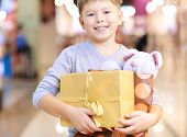 Portrait of happy child holding paperbag with teddy bear and giftbox