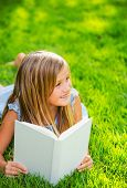 Adorable cute little girl reading book in the garden, outside on grass