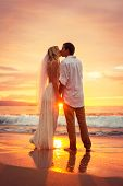 Just married couple kissing on tropical beach at sunset, Hawaii Beach Wedding, Intimate loving momen