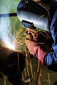 stock photo of pipe-welding  - Welding worker doing welding at pipe in workshop - JPG