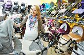 image of buggy  - Young pregnant woman choosing baby carriage or pram buggy for newborn at shop store - JPG