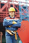 builder worker in uniform and safety protective equipment at construction site in front of metal con