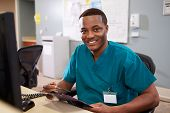 stock photo of scrubs  - Portrait Of Male Nurse Working At Nurses Station - JPG