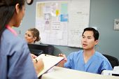 Male And Female Nurse In Discussion At Nurses Station
