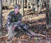 foto of hunter  - bow hunter with a whitetail doe dressed in camouflage - JPG