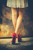 pic of short legs  - woman legs in red high heel shoes and short skirt outdoor shot against old metal door - JPG