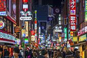 TOKYO, JAPAN - DECEMBER 24, 2012: Crowds walk through Shibuya. The district is a youth and fashion c
