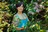 stock photo of lilac bush  - Portrait of a beautiful brunette girl who stands in the lilac bushes - JPG