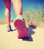 an athletic pair of legs running on a path during sunrise or sunset - healthy lifestyle concept  done with an instagram filter