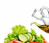Healthy Vegetable Salad with Olive oil dressing isolated on white background. Pouring Olive oil. Healthy vegetarian food. Vegan. Diet, dieting concept. Lettuce, tomatoes, cucumbers. Organic bio food