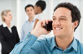 Closeup Of Businessman Talking On Cell Phone In Front Of Colleague