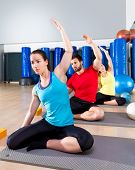 Pilates exercise the mermaid stretching obliques people group at fitness gym